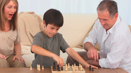 xadrez : A game of chess between a grandfather and his grandson in the living room