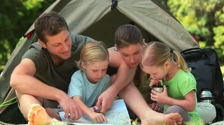 kamp : Father explaining a map to his little son while sitting with his family outside their tent