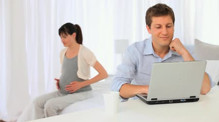 genç çift : Pregnant woman stroking her belly while her boyfriend working