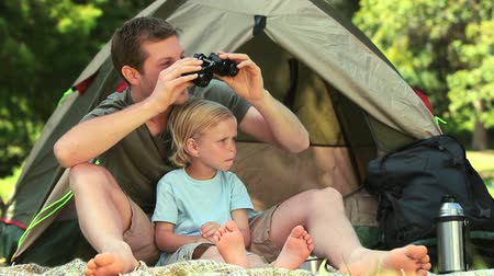 tourism : Father and son using binoculars to look at something outside their tent in the park