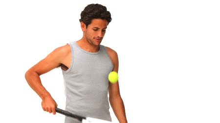 adam : Dark-haired man with a racket and tennis ball isolated on a white background Stok Video
