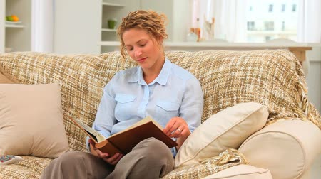 think big : Casual curly haired woman looking at an album on her sofa Stock Footage
