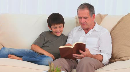 ül : Casual man reading a book with his grandson on the sofa
