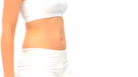 com escamas : Woman measuring her waist against a white background Stock Footage