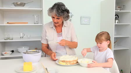 cooks : Grandmother baking with her granddaughter Stock Footage