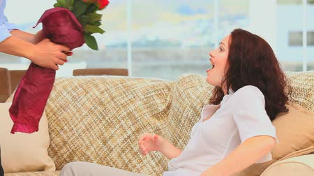 bouquets : Man giving a bunch of flowers to his wife on their couch