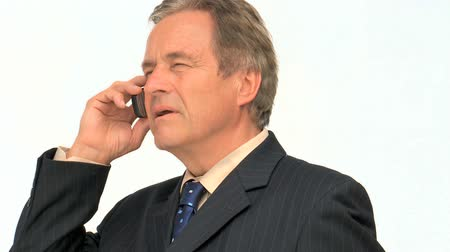 cellphone : Aged businessman in suit taking a phone call against a white background