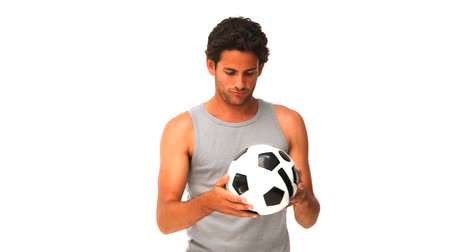 trik : Casual man playing soccer against a white background
