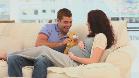 kobieta w ciąży : Lovely couple playing with a teddy bear on their sofa Wideo