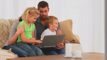 carinho : Cute family looking at a laptop in the living room