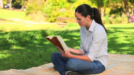 lefekvés : Attractive woman reading a book  while sitting on a rug in a park