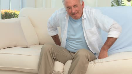 stary : Retired man having a back pain on his sofa