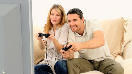 konsol : Young couple playing a video game with two joysticks