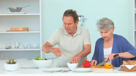 salad : Elderly couple cooking together in the kitchen