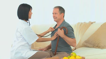 próba : Asian nurse listening to heartbeat of an elderly man in the living room