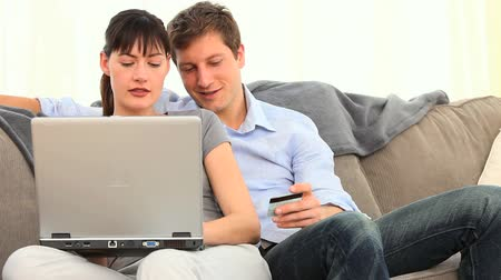 купить : Pretty couple using a credit card on internet in the living room