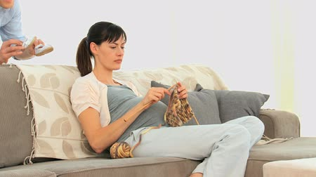 вязание : Couple playing with little shoes on a couch