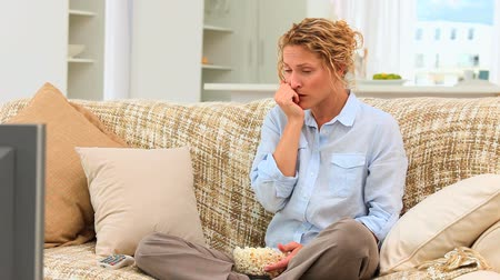 megrémült : Curly haired woman watching a scary movie in her living room