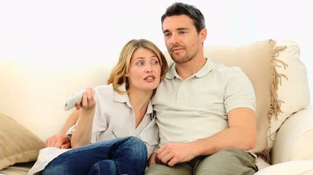 home life : Pretty couple watching tv on their sofa