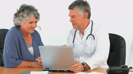 diagnóstico : Doctor and his patient looking at the laptop