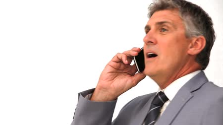 гнев : Angry businessman phoning isolated on a white background Стоковые видеозаписи