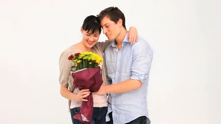 bouquets : Loving couple with a brunch of flowers isolated on a white background Stock Footage