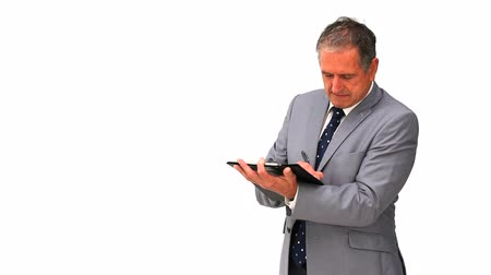 impostos : Mature businessman taking notes isolated on a white background