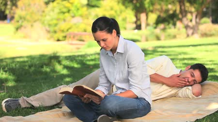 otuzlu yıllar : Woman reading a book on a rug in a park while her boyfriend is taking a nap Stok Video