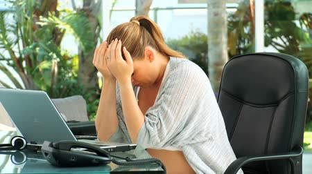 stres : Very tired pregnant woman at an office touching her back