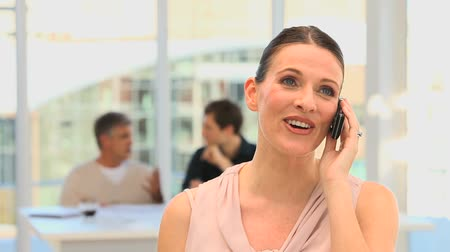 брюнет : Casual woman making a phone call with people on the background Стоковые видеозаписи