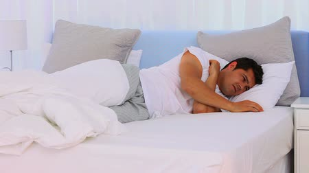 cold : Sick brown-haired man blowing his nose lying on his bed at morning