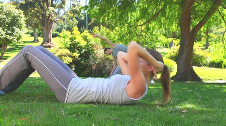 esneme : Athletic couple doing exercises in the shade of a tree in the park Stok Video