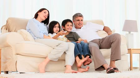 guy home : Family watching a movie with popcorn in the living room