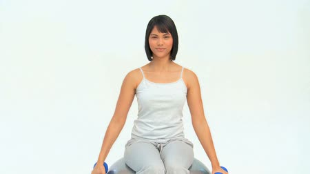 levantamento de pesos : Asian woman with dumbbells on a gym ball against a white background