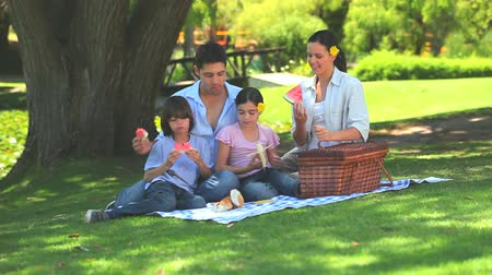 пикник : Happy  family eating fruit while picnicking on a rug under a tree