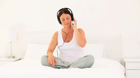 umma : Pregnant woman listening to music on her bed Stok Video