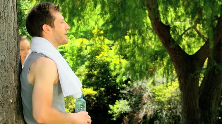 estilo de vida saudável : Man leaning against a tree giving his girfriend a drink and a towel after jogging