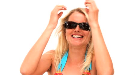 tonları : Cute lady in swimsuit with sunglasses against a white background Stok Video