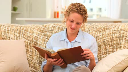 фото : Relaxed woman looking at an album on the sofa