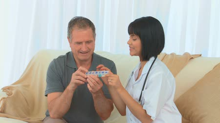 segítség : Asian nurse giving some explanations about pills to her patient Stock mozgókép