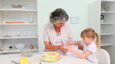 cooks : Grandmother with her granddaughter baking Stock Footage