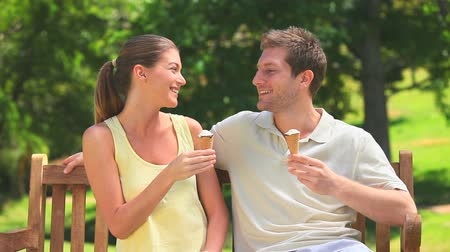 creams : Relaxed couple eating ice creams on a park bench Stock Footage