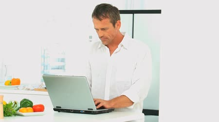 bate papo : Middle aged man working on his laptop in the kitchen Stock Footage