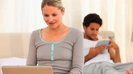 download : Young couple in their bedroom with a book and laptop