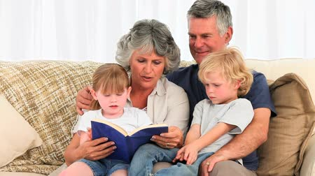 hareketli : Grandparents reading a book to their grandchildren