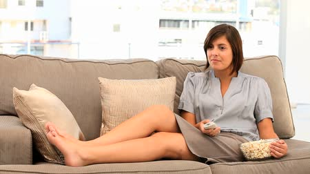 girl : Casual brunette woman watching tv with popcorn in her living room