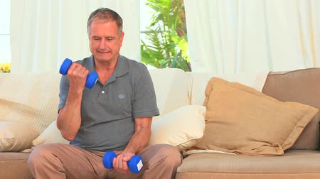 exercícios : Dynamic male with dumbbells sitting on his couch