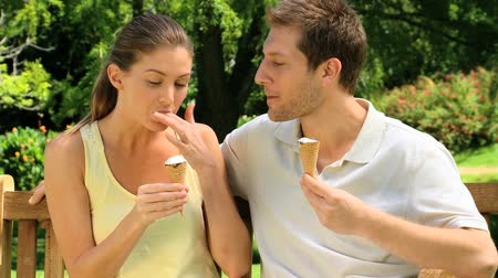 creams : Young couple enjoying chatting and eating ice creams on a park bench