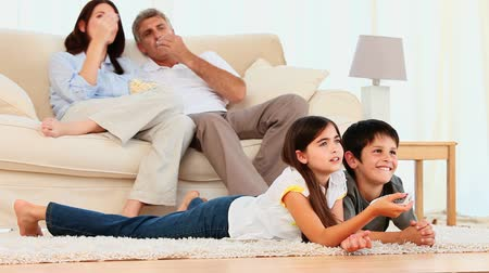 négy ember : Family watching a movie in the living room