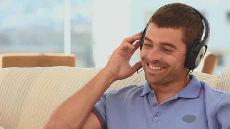 armoni : Casual man listening to music with headphones in his living room